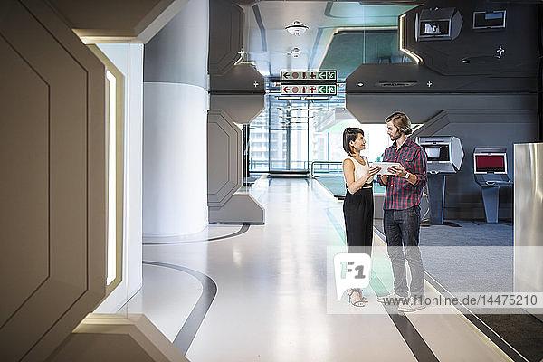 Geschäftsleute  die in einem Bürokorridor diskutieren