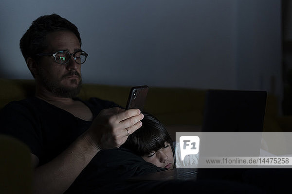 Father using laptop and cell phone on couch at night with daughter sleeping