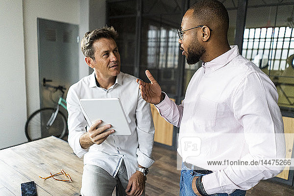 Two businessmen with tablets having a meeting in loft office