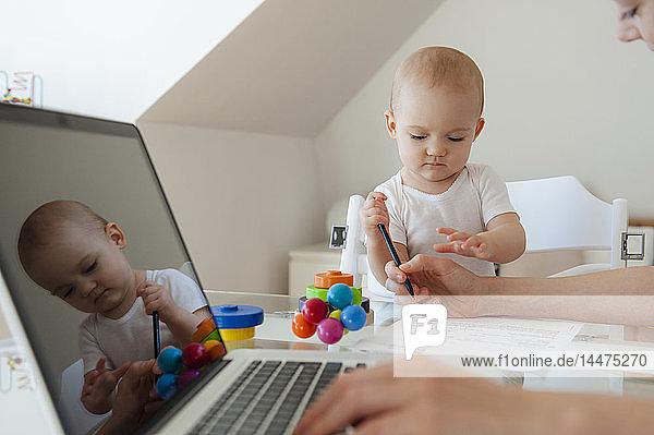 Kleine spielende Tochter und Mutter mit Laptop am Tisch zu Hause