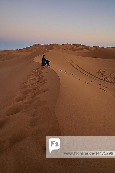 Marokko  Frau sitzt in der Dämmerung auf einer Wüstendüne