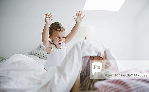 Happy toddler son playing with mother in bed at home