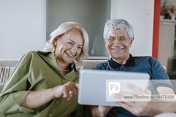 Glückliches älteres Ehepaar sitzt zu Hause auf der Couch und teilt sich ein Tablet