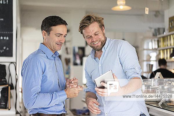 Zwei lächelnde Geschäftsleute teilen sich ein Tablett