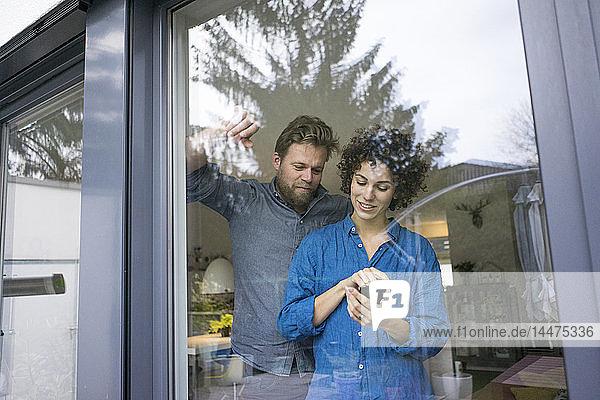 Ehepaar zu Hause hinter dem Fenster mit Mobiltelefon