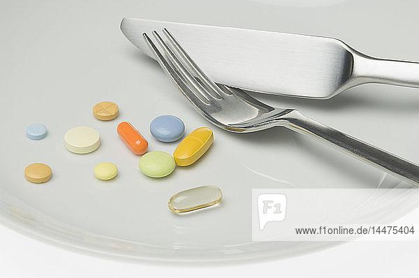 Pillen auf einem Teller mit Besteck