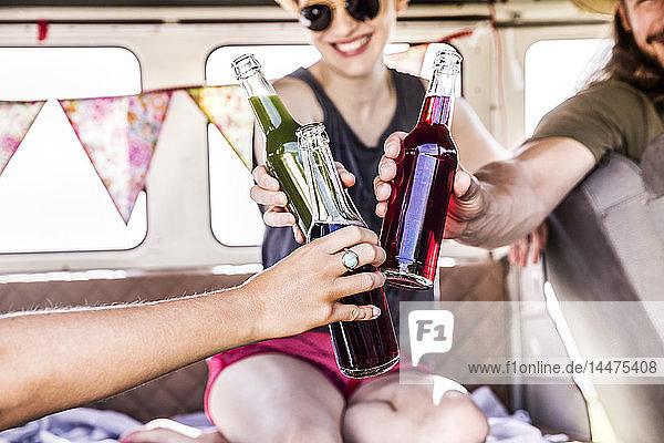 Glückliche Freunde in klirrenden Flaschen im Lieferwagen