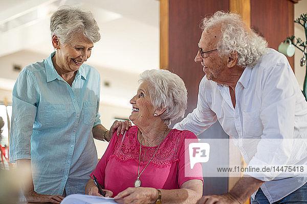 Ältere Frau unterzeichnet einen Vertrag  Freunde beruhigen sie