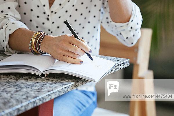 Nahaufnahme einer Frau  die in einem Notizbuch auf den Tisch schreibt