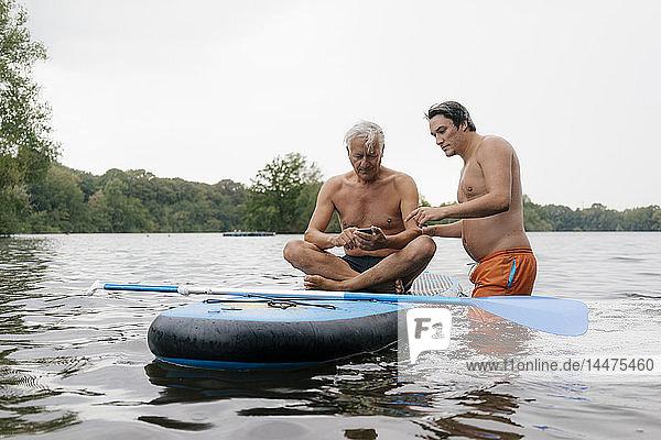 Älterer und jüngerer Mann mit SUP-Board auf einem See mit Handy