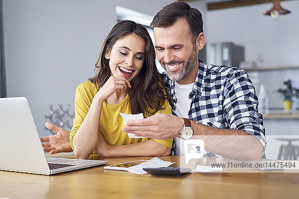 Couple sitting at dining table  using laptop  checking bills