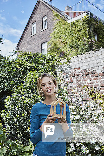 Portrait of woman in garden of her home holding house model