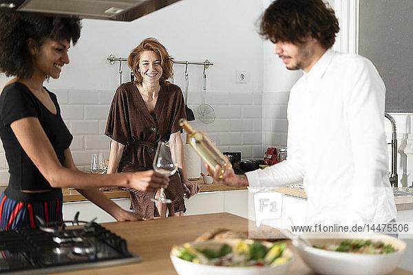 Freunde stehen in der Küche und trinken Weißwein