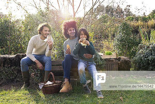 Glückliche Familie sitzt im Garten  macht eine Pause  isst Sandwiches