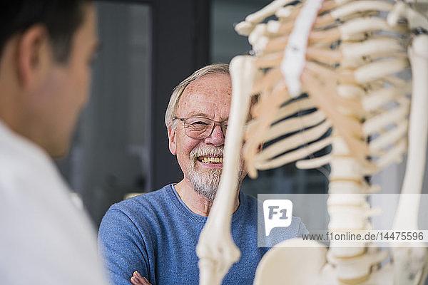 Lächelnder älterer Patient mit Arzt in medizinischer Praxis mit anatomischem Modell