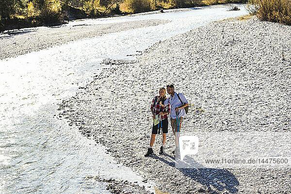 Österreich,  Alpen,  Paar auf Wanderung am Bach stehend