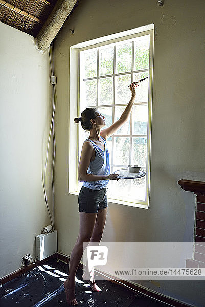 Young woman renovating her home painting the window frame