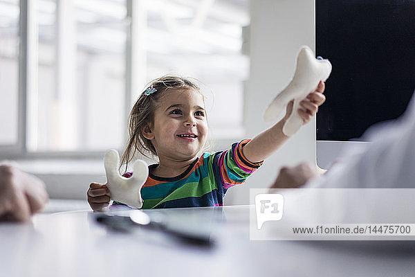Porträt eines lächelnden Mädchens mit Zahnmodell am Schreibtisch in der Arztpraxis