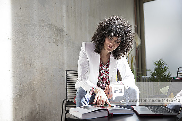 Businesswoman sitting on a chair at concrete wall reading book