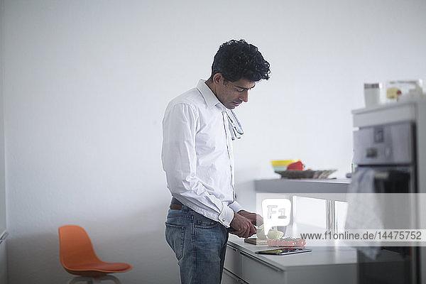 Man standing in kitchen preparing vegetables
