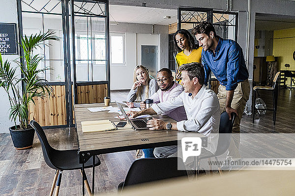 Business team having a meeting in loft office looking at laptop together