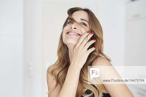 Glückliche junge Frau spielt mit ihren Haaren