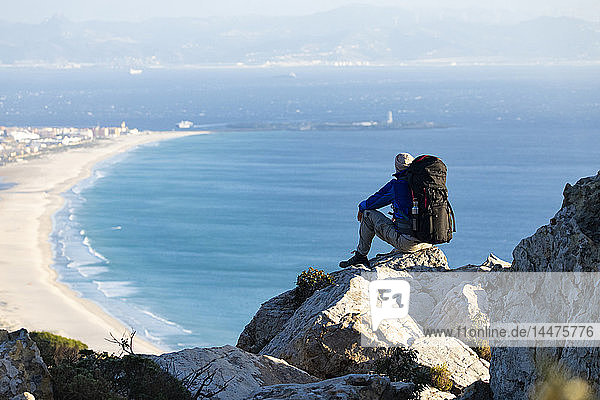 Spain  Andalusia  Tarifa  man on a hiking trip at the coast sitting on a rock looking at view