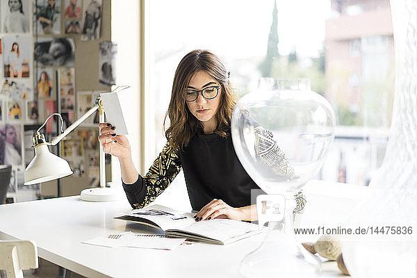 Porträt eines jungen Designers  der sich in einem Atelier ein Buch ansieht
