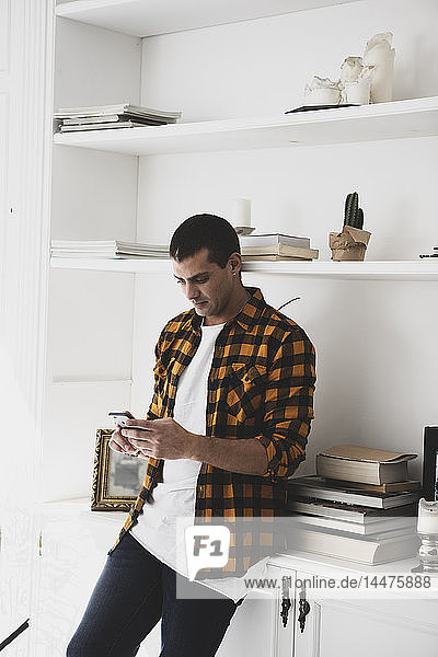 Young man standing at a shelf using cell phone