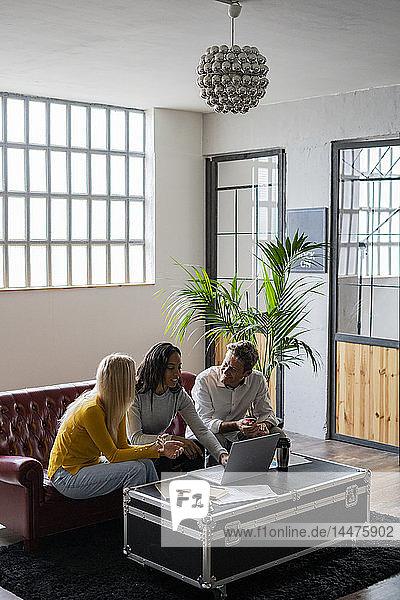 Geschäftsteam mit Laptop auf der Couch sitzend im Loft-Büro
