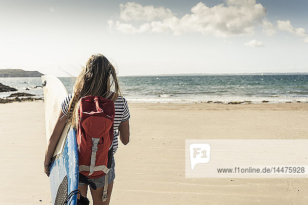Young woman with backpack  walking on the beach  carrying surfboard