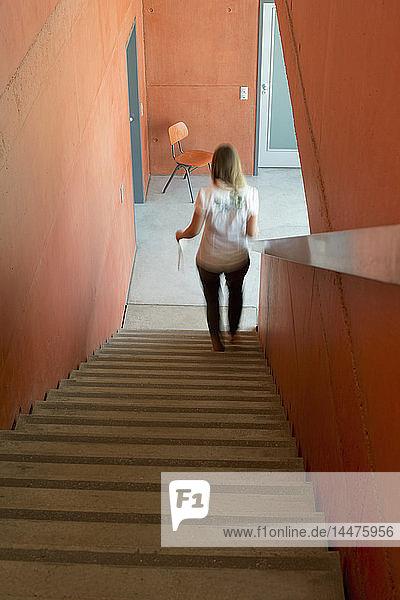 Rückenansicht einer Frau  die eine Treppe hinuntergeht