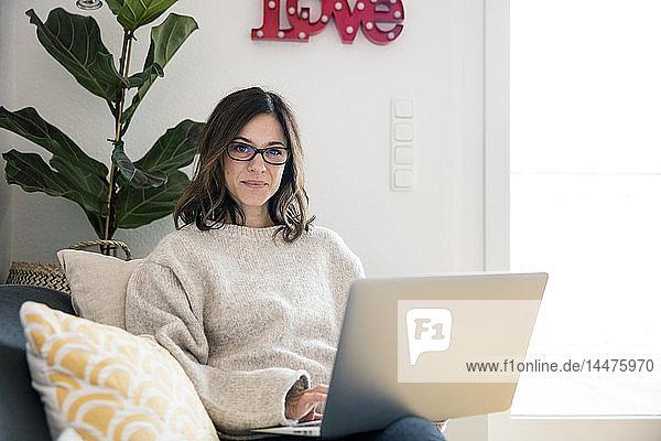 Frau sitzt auf ihrer Couch  surft im Internet  benutzt Laptop