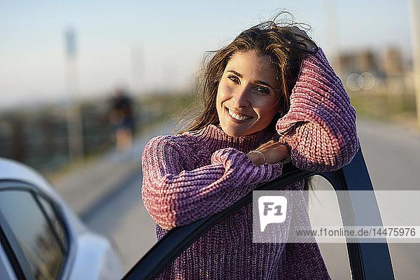 Porträt einer lächelnden Frau  die sich an eine Autotür lehnt
