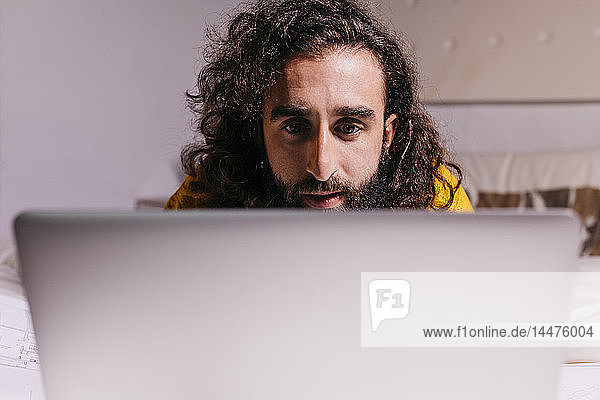 Young man in bed at home using laptop