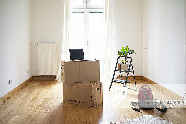 Piled cardboard boxes and laptop in an empty room
