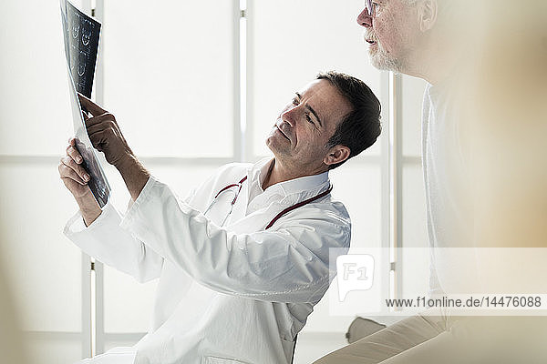 Arzt bespricht MRT-Bild mit Patient in medizinischer Praxis