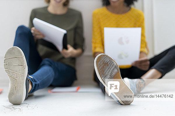 Kollegen im Coworking Space  die Geschäftslösungen diskutieren  auf dem Boden sitzend