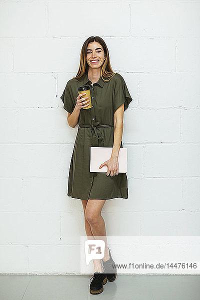 Porträt einer lächelnden jungen Frau mit Tablette und Kaffee zum Mitnehmen  die an einer Ziegelmauer steht