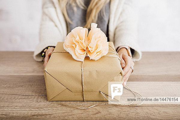 Junge Frau zeigt ein verpacktes Geschenk in ihrem Atelier