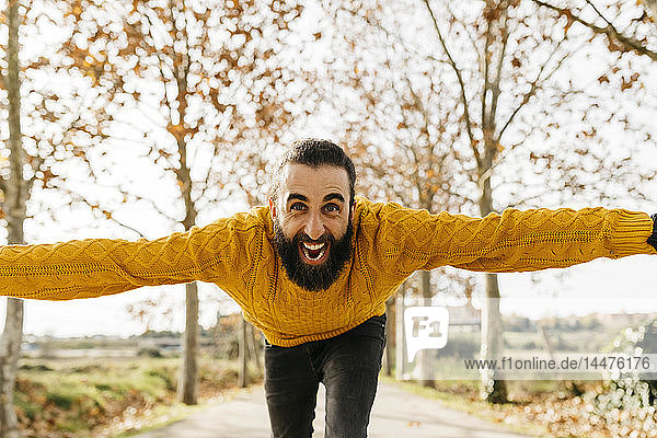 Junger Mann mit offenen Armen und glücklich im Herbst in einem Park
