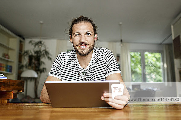 Young man with a bun sitting at home  using digital tablet