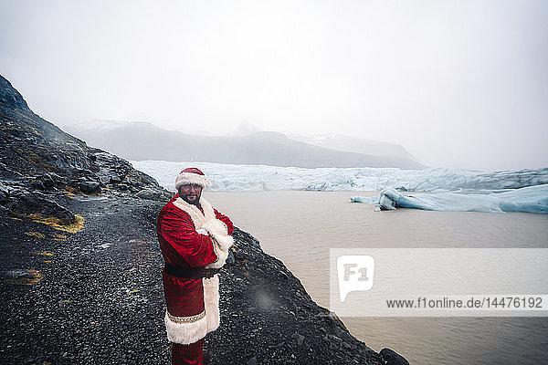 Island  lächelnder Weihnachtsmann vor dem Gletscher stehend