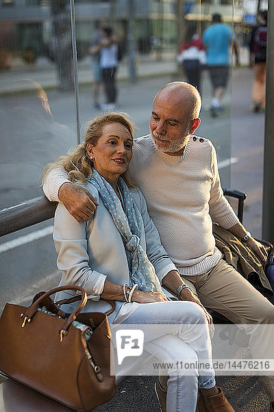 Spain  Barcelona  senior couple with baggage sitting at tram stop in the city