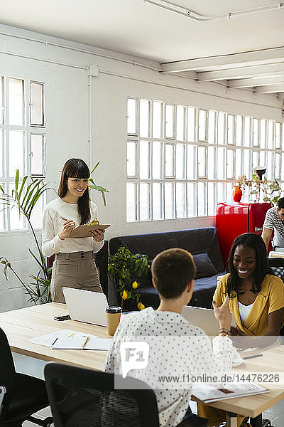 Smiling woman with clipboard among colleagues in office