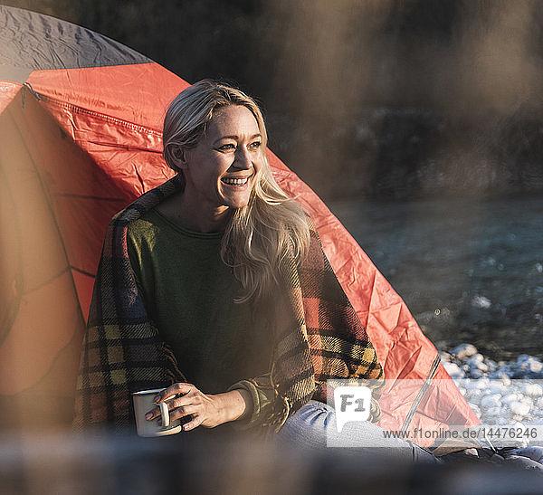 Ältere Frau zeltet  sitzt vor dem Zelt