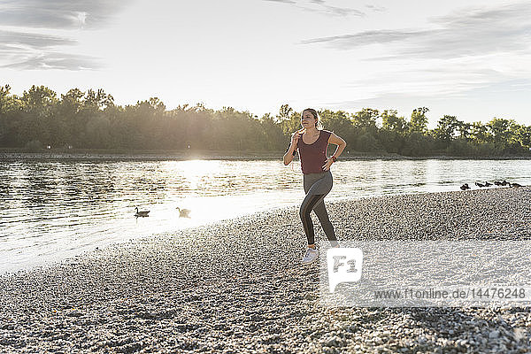 Young woman jogging at he river