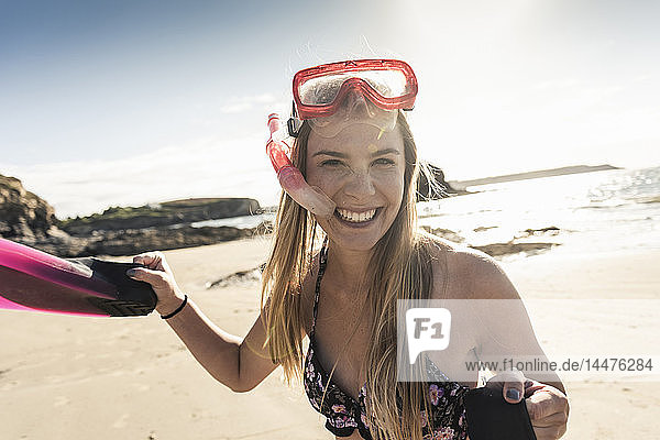 Happy young woman with snorkelling equipment  running on the beach