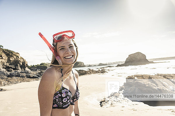 Happy young woman with snorkelling equipment on the beach  portrait