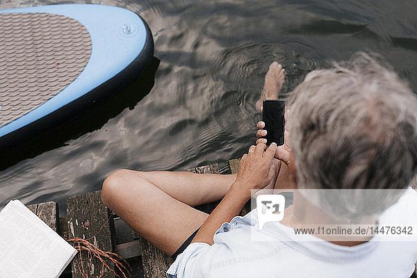 Älterer Mann sitzt auf einem Steg an einem See und benutzt sein Handy